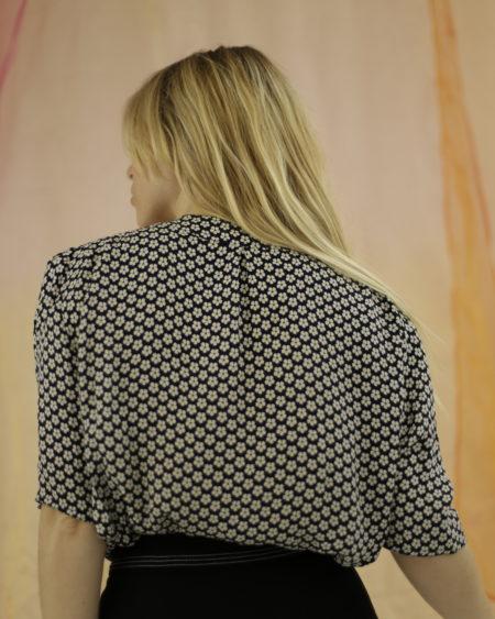 Blouse Nina Ricci Bleue à fleurs blanches, manches courtes, boutons assortis