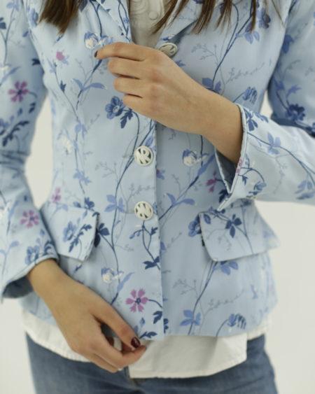 Veste Nina Ricci. Bleu ciel avec fleurs imprimées, épaulettes, boutons siglés, deux poches à l'avant, made in France.
